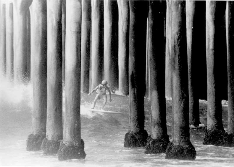 Tatsächlich versuchen die Surfer sich schon seit zig Jahren an der Line zwischen den Pierpfeilern, wie das Foto aus den 70er Jahren beweist. Alerdings forderte diese Mutprobe im Lauf der Jahre auch Todesopfer. Credit: City of Huntington Beach Archives.