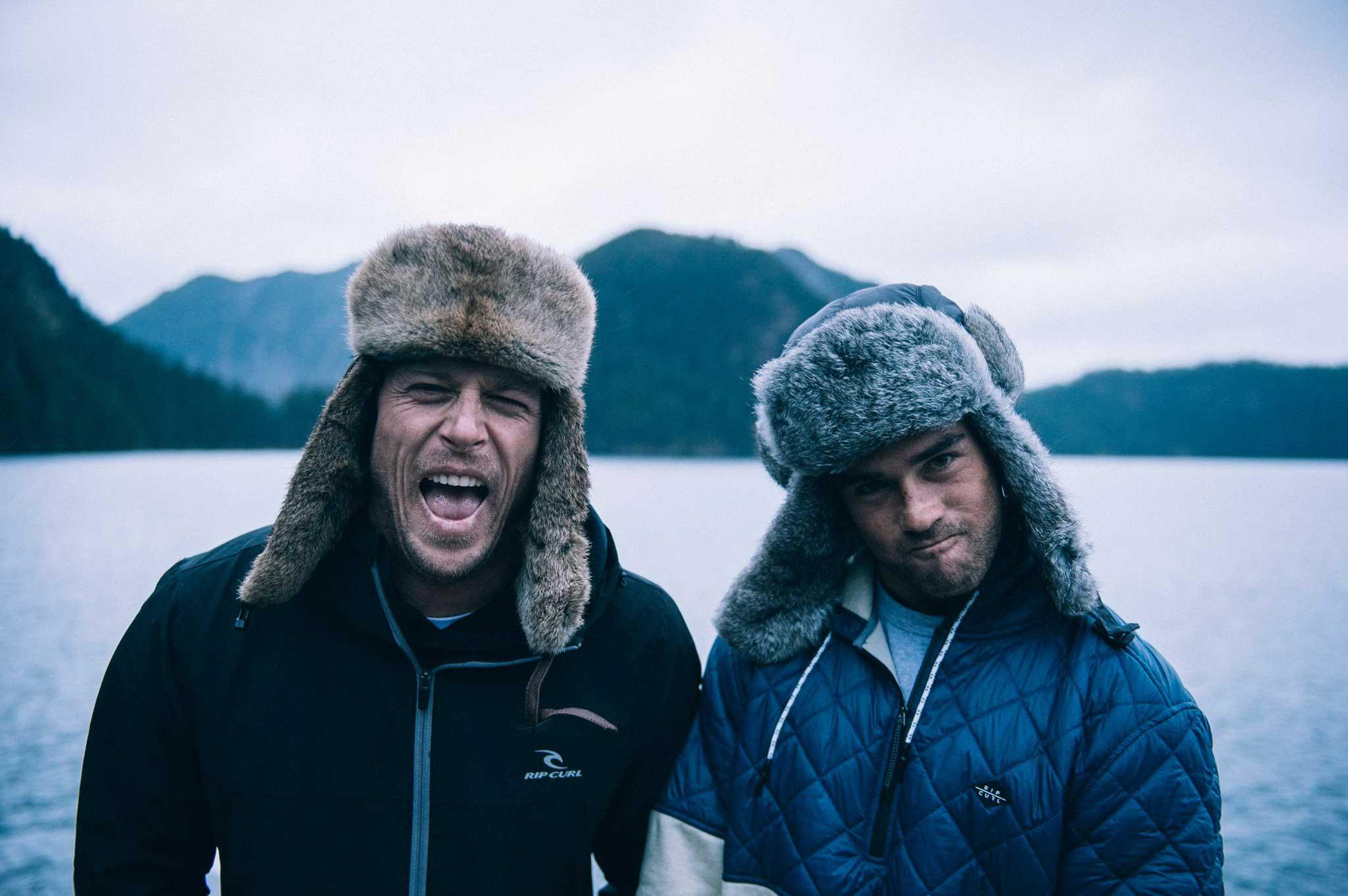 Zwei Männer, die dafür bezahlt werden, zu surfen.