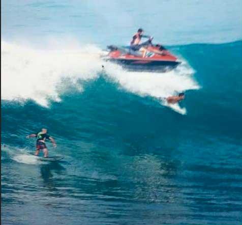 Der Jetski schießt von hinten heran, als der Surfer gerade einen Takoff macht.